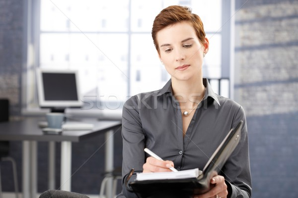 Businesswoman at work taking notes Stock photo © nyul