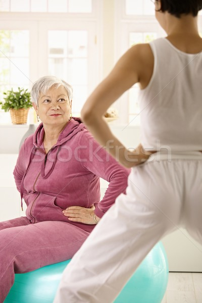 Elderly woman looking at personal trainer Stock photo © nyul