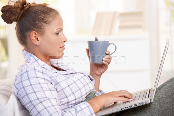 Young woman using laptop in bed drinking tea Stock photo © nyul