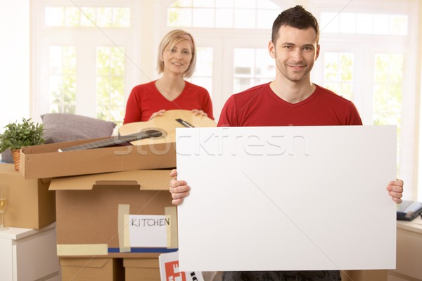 Stock photo: Smiling couple surrounded with boxes in new house