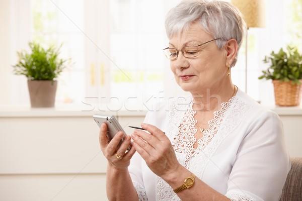 Nowoczesne starszy kobieta pda portret domu Zdjęcia stock © nyul