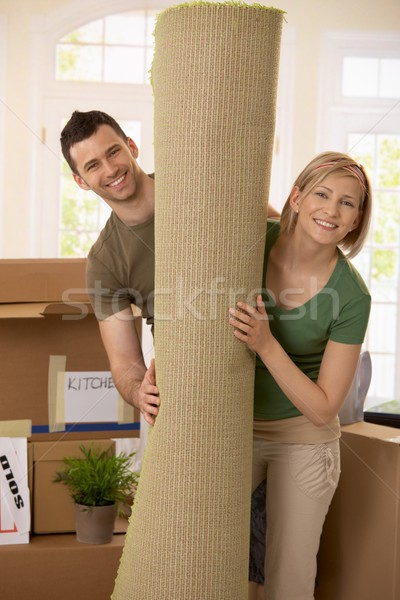Portrait of couple with rolled up carpet Stock photo © nyul