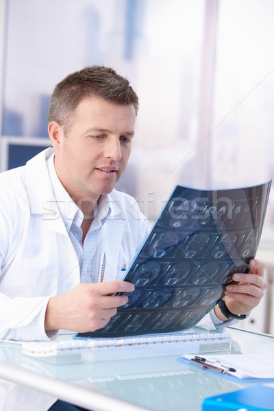Male doctor looking at x-ray image in office Stock photo © nyul