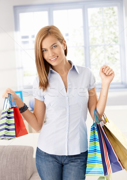 Attractive girl arriving from shopping smiling Stock photo © nyul