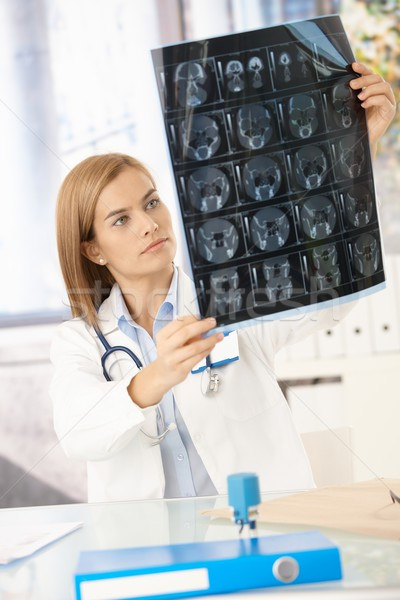 Young female doctor studying x-ray image Stock photo © nyul