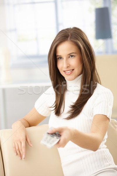 Felice donna telecomando seduta divano home Foto d'archivio © nyul