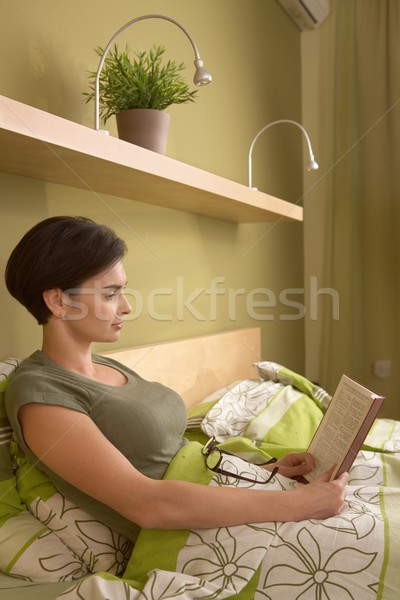 Mid-adult woman reading in bed Stock photo © nyul