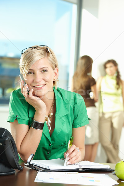 Jeunes femme d'affaires parler mobiles séance bureau Photo stock © nyul