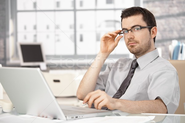Young businessman sitting at desk using laptop Stock photo © nyul