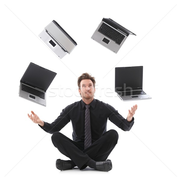 Stock photo: Businessman juggling with laptops