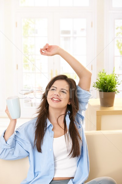 Stock photo: Girl laughing with tea mug in hand