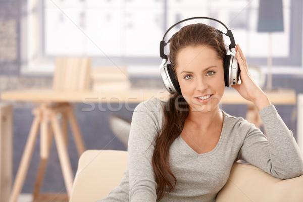 ストックフォト: 魅力的な女の子 · 音楽を聴く · ホーム · 笑みを浮かべて · 座って · ソファ