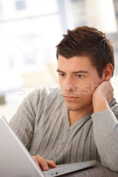 Stock photo: Goodlooking guy using laptop