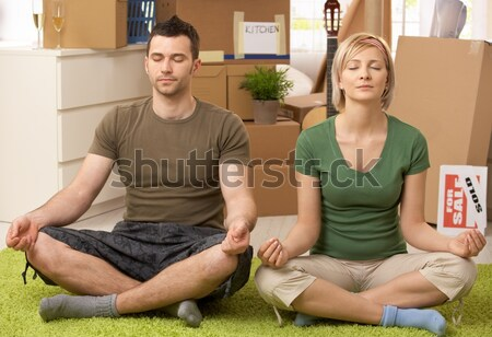 Smiling couple roll out carpet together Stock photo © nyul