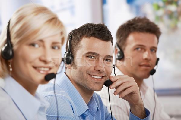 Müşteri hizmetleri mutlu genç konuşma kulaklık göz teması Stok fotoğraf © nyul