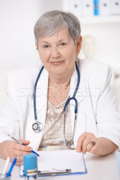 Stock photo: Senior doctor working at desk
