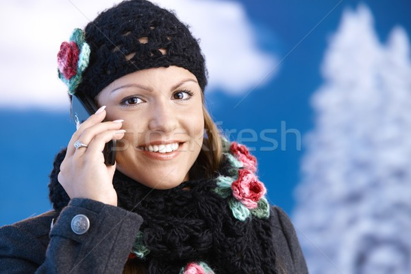 Pretty girl dressed up warm smiling using mobile Stock photo © nyul