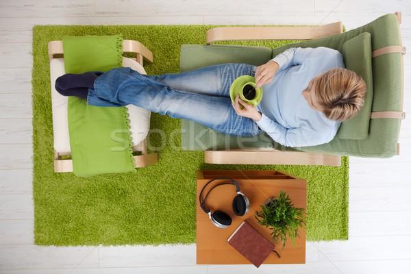 Сток-фото: женщину · кофе · домой · сидят · кресло · скрещенными · ногами