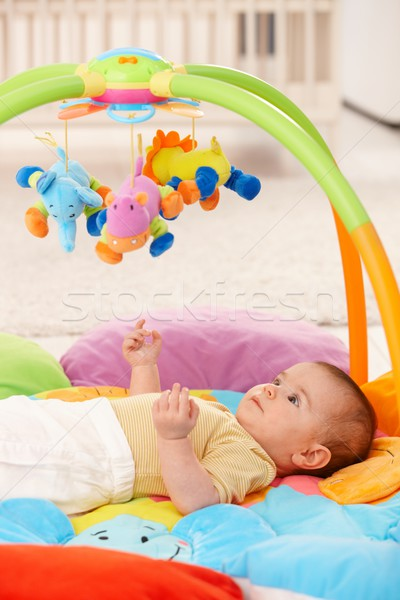 Stock photo: Baby girl on playmat