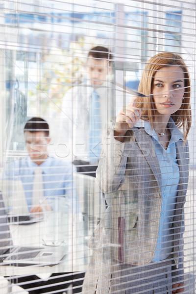 Pretty businesswoman peeping through blind Stock photo © nyul