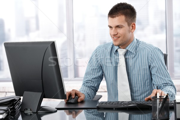 Stock photo: Young businessman working in modern office smiling