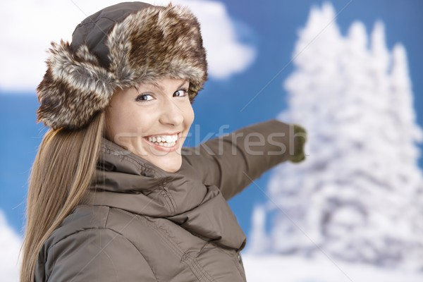 Pretty girl dressed up for winter smiling pointing Stock photo © nyul