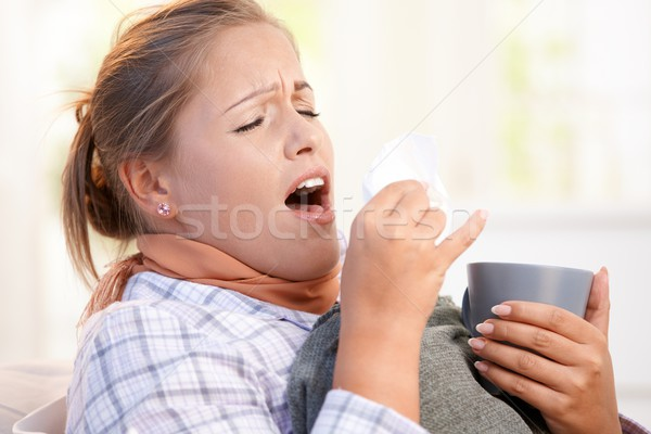 Young female having flu laying in bed sneezing Stock photo © nyul
