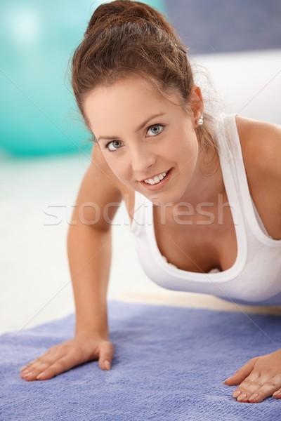 Portrait of attractive girl exercising on floor Stock photo © nyul