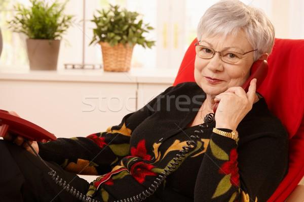 Idős hölgy telefon ül nappali fotel Stock fotó © nyul