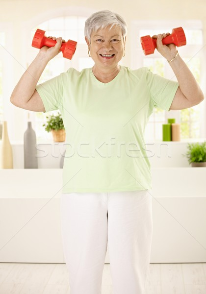Energetic elderly woman training at home Stock photo © nyul