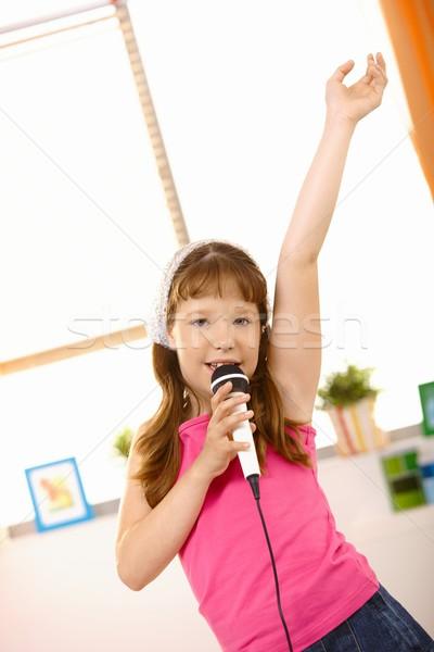 Fiatal lány énekel kéz felfelé magas mikrofon Stock fotó © nyul