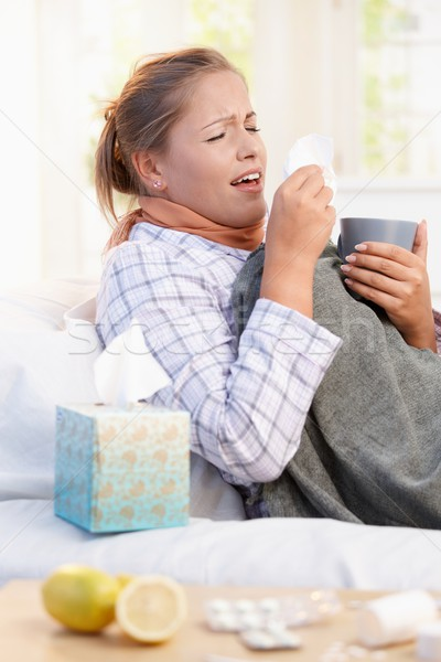 Young woman having flu laying in bed sneezing Stock photo © nyul