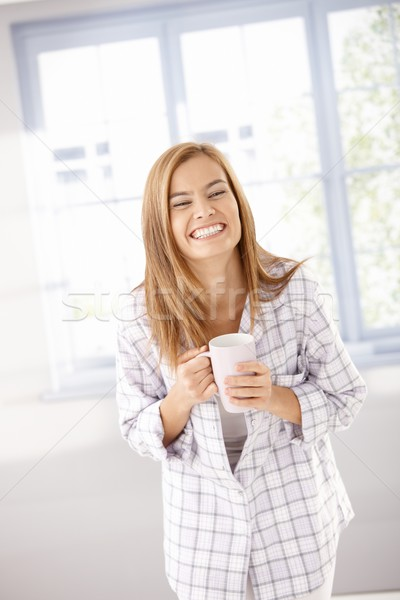 Young female laughing happily in pyjama Stock photo © nyul