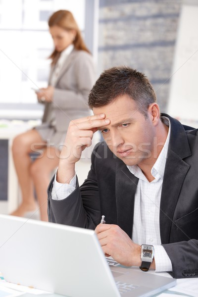Troubled businessman working on laptop Stock photo © nyul