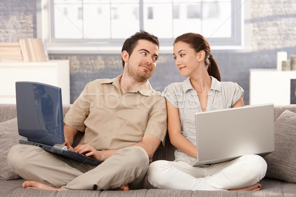 Stock photo: Young couple sitting on sofa using laptop smiling