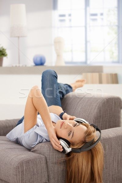 Attractive female laying on sofa listening music Stock photo © nyul