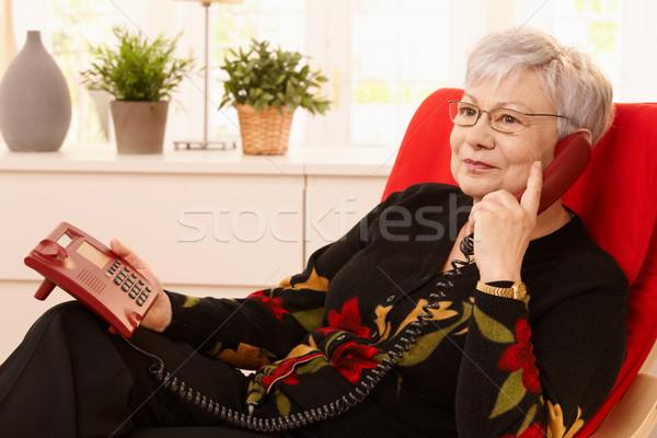 Gepensioneerde vrouw telefoon vergadering fauteuil woonkamer Stockfoto © nyul