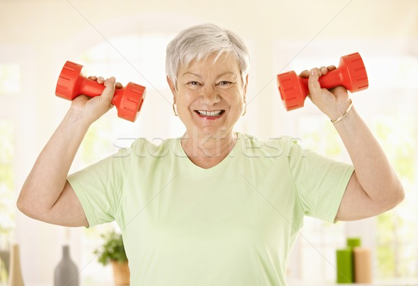 Energetic senior woman with dumbbels Stock photo © nyul