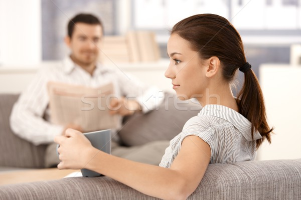 Stock photo: Young woman sitting on sofa man in background