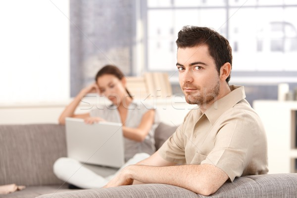 Stock photo: Young couple sitting on sofa at home