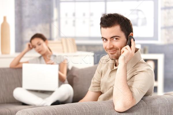 Fiatalember beszél mobil mosolyog ül kanapé Stock fotó © nyul