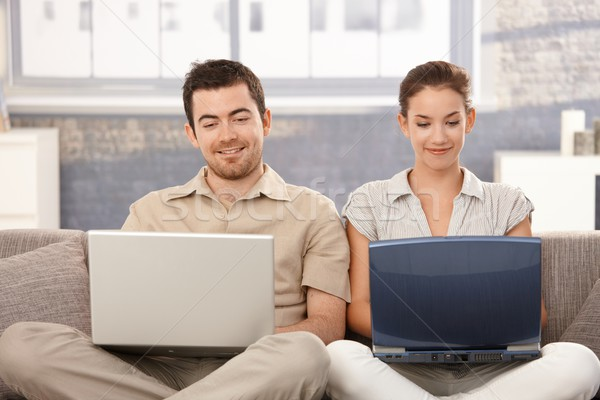 Stock photo: Young couple browsing internet at home smiling