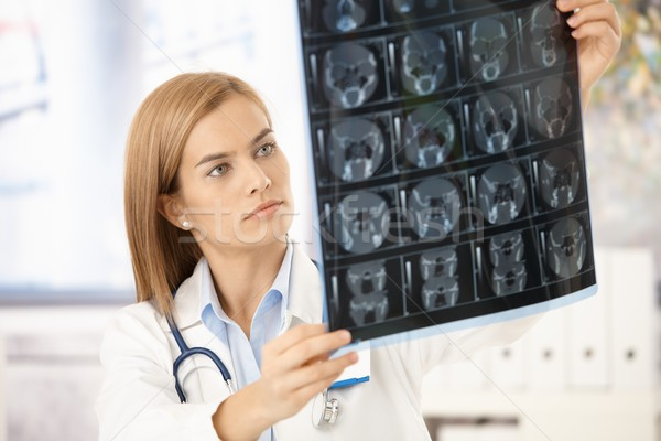 Young radiologist looking at x-ray image Stock photo © nyul