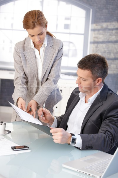 Good-looking boss signing contract at desk Stock photo © nyul
