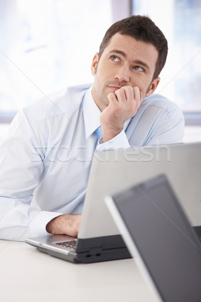Young businessman daydreaming at desk Stock photo © nyul