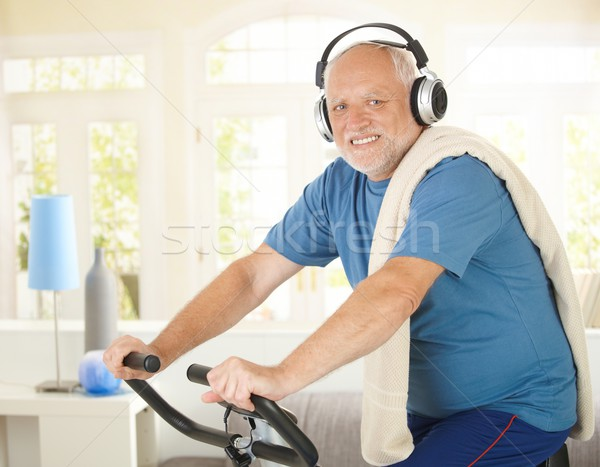 Active pensioner doing spinning with music Stock photo © nyul