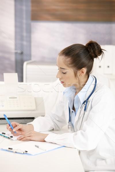 Female doctor writing at desk Stock photo © nyul