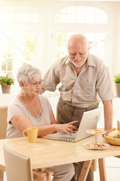 Foto stock: Ancianos · Pareja · sonriendo · usando · la · computadora · portátil · ordenador