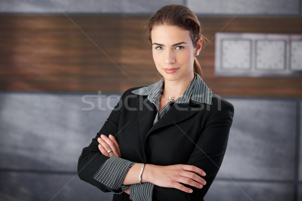 Well-dressed woman standing arms crossed in lobby Stock photo © nyul