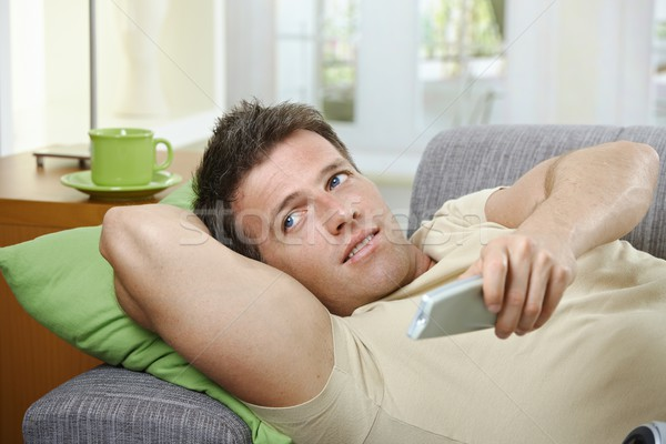 Smiling man on sofa using remote control Stock photo © nyul